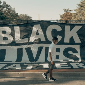 Person walks past Black Lives Matter banner